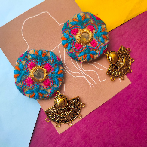 Threadwork on fabric with golden hanging earrings
